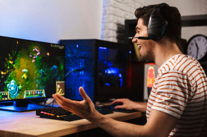 Image of cheerful gamer man playing video games on computer, wearing headphones and using backlit colorful keyboard