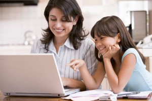3602837 - woman and young girl in kitchen with laptop and paperwork smiling
